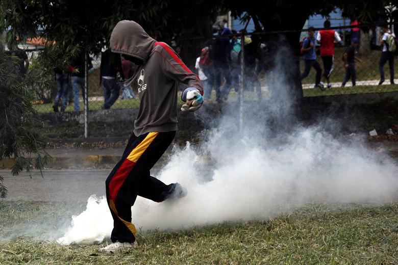 A demonstrator kicks back a tear gas canister during a protest against Venezuelan President Nicolas Maduro's government in San Cristobal, Venezuela. REUTERS/Carlos Eduardo Ramirez