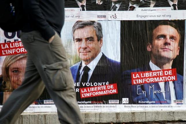 4月6日、最新の世論調査によると、フランス大統領選は中道系独立候補のマクロン前経済相と極右政党・国民戦線(FN)のルペン党首が依然リードを保っている。ただ、急進左派のメランション氏が急速に追い上げていることも明らかになった。写真は大統領候補らのポスター。パリで5日撮影(2017年 ロイター/Charles Platiau)