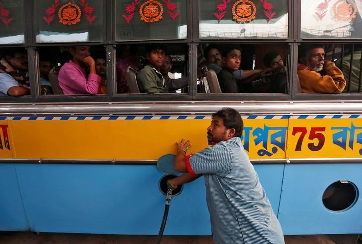 A worker fills a public bus with diesel as passengers look on, at a fuel station in Kolkata, India, February 1, 2017. REUTERS/Rupak De Chowdhuri