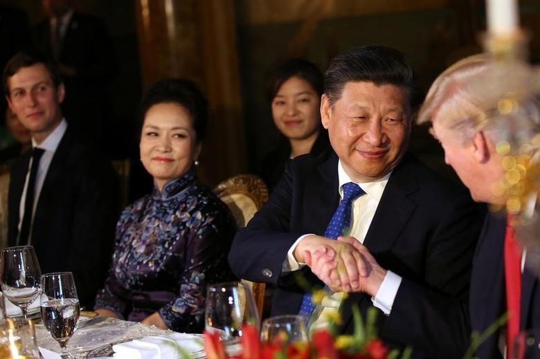 Chinese President Xi Jinping shakes hands with U.S. President Donald Trump as he is accompanied by China's first lady Peng Liyuan (2nd L) during a dinner at the start of a summit between President Trump and President Xi at Trump's Mar-a-Lago estate in West Palm Beach, Florida, U.S., April 6, 2017. REUTERS/Carlos Barria