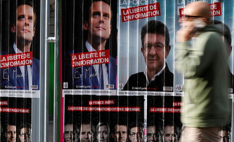 A man walks past campaign posters of candidates Jean-Luc Melenchon of the Parti de Gauche and Emmanuel Macron head of the political movement En Marche! (Onwards!), two of the eleven candidates who run in the 2017 French presidential election in Paris, France, April 5, 2017. REUTERS/Gonzalo Fuentes