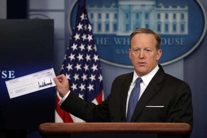White House Press Secretary Sean Spicer shows a check from U.S. President Donald Trump's salary which will be donated to the National Park Service during a daily press briefing at the White House in Washington, U.S., April 3, 2017. REUTERS/Carlos Barria