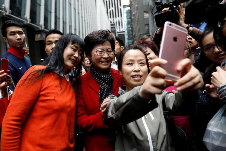 People take selfies with Carrie Lam, chief executive-elect, a day after she was elected in Hong Kong, China March 27, 2017.REUTERS/Tyrone Siu/Files