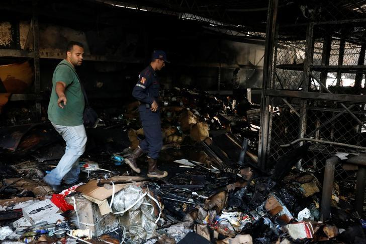 A fireman and another man walk past burned debris in a warehouse in the building where the offices of Venezuelan opposition leader and Governor of Miranda state Henrique Capriles are located, in Caracas, Venezuela April 8, 2017. REUTERS/Carlos Garcia Rawlins