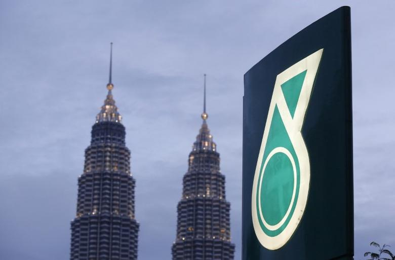 The logo of a Petronas fuel station is seen with the Petronas Twin Towers in the background in Kuala Lumpur, Malaysia. Picture taken February 10, 2016. REUTERS/Olivia Harris