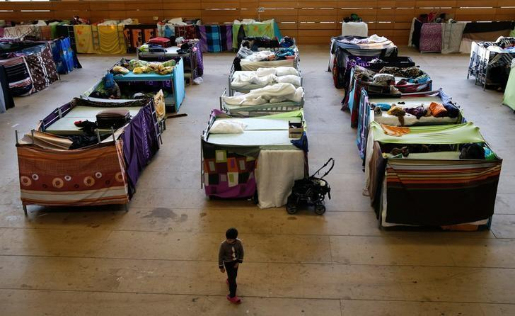 A migrant child walks at the sports hall of the Jane-Addams high school which has been transformed into a refugee shelter in Berlin's Hohenschoenhausen district, Germany, February 2, 2016. REUTERS/Fabrizio Bensch/File Photo