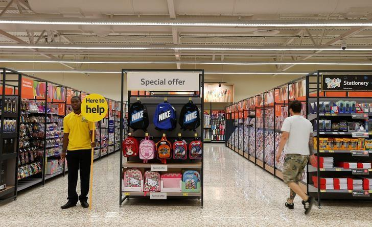FILE PHOTO: A customer service representative stands in an aisle at a Tesco Extra supermarket in Watford, north of London August 8, 2013.  REUTERS/Suzanne Plunkett/File Photo