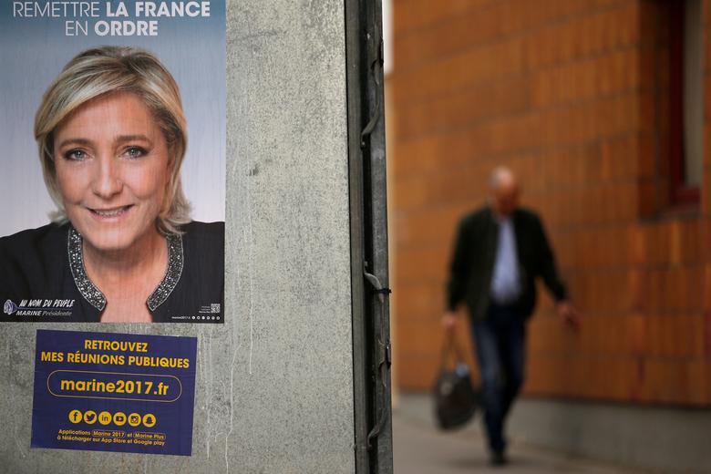 A man walks past a campaign poster of Marine Le Pen, French National Front (FN) political party leader and one of the eleven candidates who runs in the 2017 French presidential election, in Paris, France, April 10, 2017. REUTERS/Gonzalo Fuentes