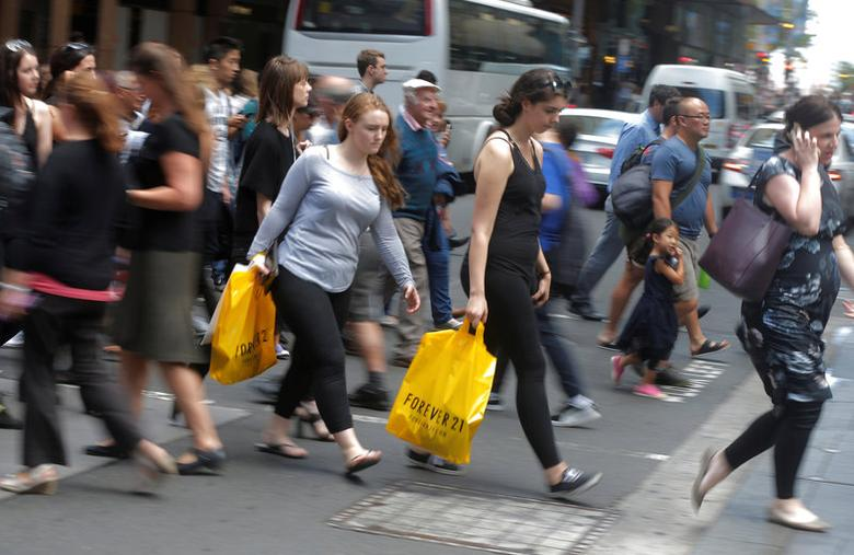 Shoppers carry their purchases across a street in Sydney's central shopping district, March 15, 2017.   REUTERS/Jason Reed