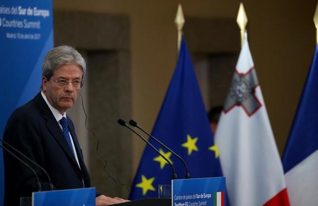 4月11日、イタリア政府は、2017年に追加の財政赤字削減を実施することを承認した。また17、18年の経済成長率は引き続き小幅にとどまるとの見通しを示した。写真は10日、スペイン・マドリッドにおける南EU諸国サミットに出席、記者会見を行うジェンティローニ伊首相(2017年 ロイター/Juna Medina)
