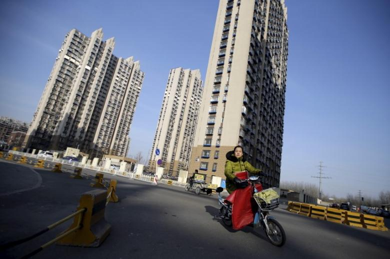 A woman rides past a residential compound in Beijing's Tongzhou district, China, February 25, 2016. REUTERS/Jason Lee