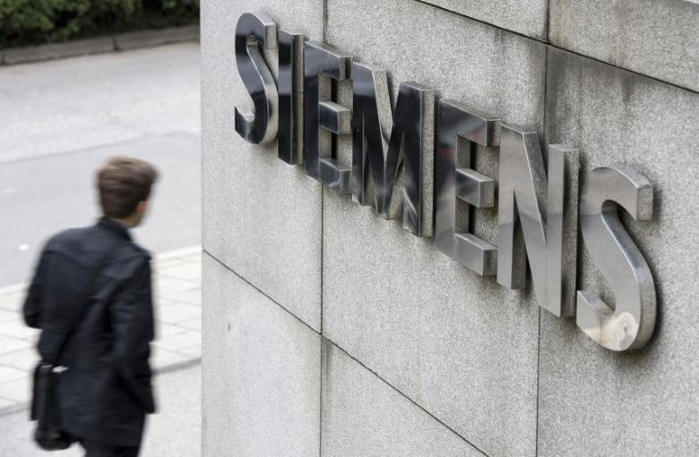 A man passes Germany's Siemens AG headquarters in Munich Perlach May 30, 2014. REUTERS/Lukas Barth