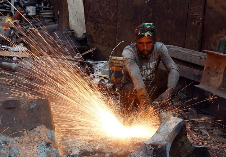 A worker uses a gas cutter at a metal workshop in an industrial area in Mumbai, India, February 10, 2017. REUTERS/Danish Siddiqui/File Photo