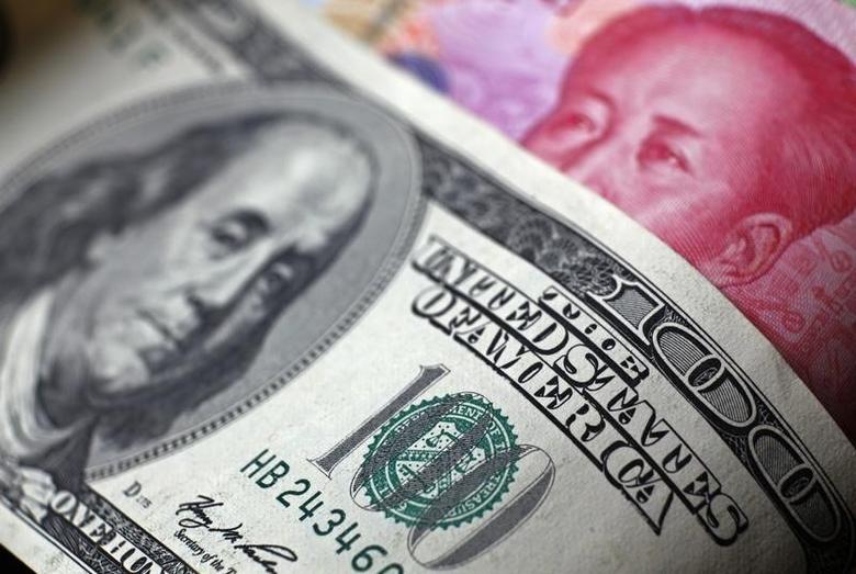 资料图片:2010年11月,人民币和美元纸币。REUTERS/Petar Kujundzic
