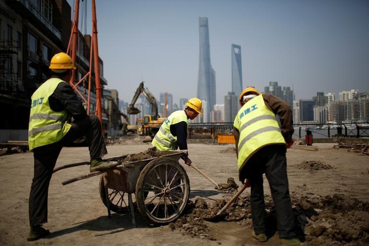 Workers work at a construction site in front of Shanghai's financial district of Pudong in Shanghai, China March 27, 2017. REUTERS/Aly Song