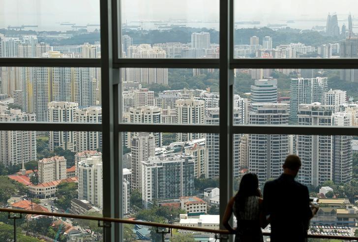 资料图片:2017年2月10日,人们从窗口远眺新加坡的写字楼和住宅区。REUTERS/Edgar Su