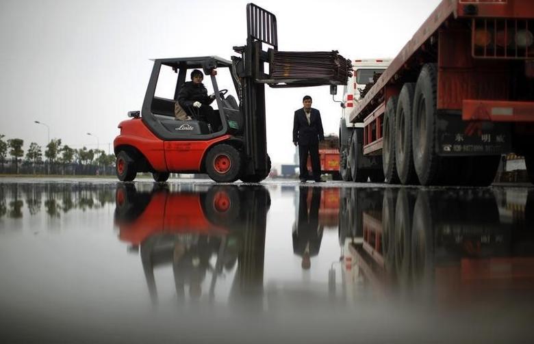 资料图片:2012年3月,上海洋山港附近一座仓库,工人在搬运铜板材。REUTERS/Carlos Barria