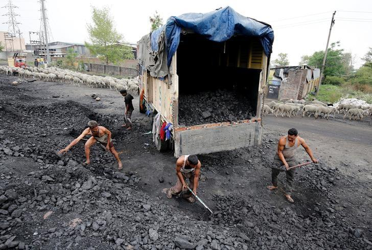 Labourers load coal onto a supply truck on the outskirts of Jammu April 6, 2017. REUTERS/Mukesh Gupta