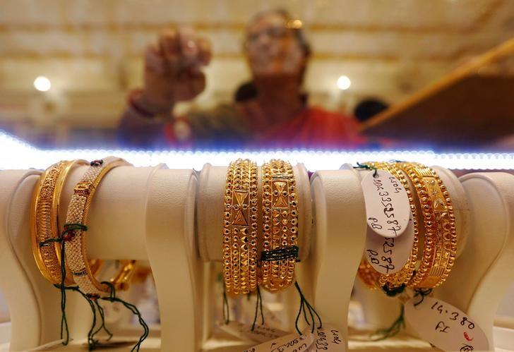 Gold bangles are on display as a woman makes choices at a jewellery showroom during Dhanteras, a Hindu festival associated with Lakshmi, the goddess of wealth, in Kolkata, India October 28, 2016. REUTERS/Rupak De Chowdhuri/File photo