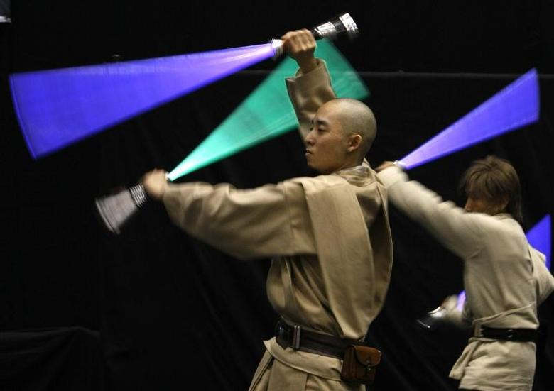 Participants dressed as Jedi Knight characters from the Star Wars movies, perform with their lightsaber props during the opening day of ''Star Wars Celebration Japan'' at the Makuhari Messe in Chiba, east of Tokyo July 19, 2008. REUTERS/Issei Kato