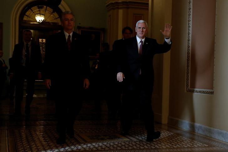 U.S. Vice President Mike Pence (R) leaves the floor of the Senate after presiding over the vote on Judge Neil Gorsuch's confirmation as an Associate Justice of the Supreme Court at the U.S. Capitol in Washington, U.S., April 7, 2017. REUTERS/Aaron P. Bernstein