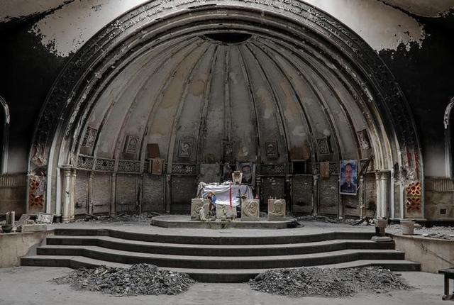An altar of a damaged church is seen in the town of Qaraqosh, south of Mosul, Iraq, April 11, 2017. REUTERS/Marko Djurica