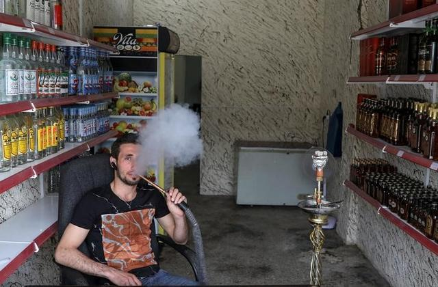 Steve Ibrahim, an alcohol shop owner, smokes in the town of Qaraqosh, south of Mosul, Iraq, April 13, 2017. REUTERS/Marko Djurica