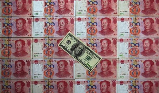 4月13日、トランプ米大統領は米紙のインタビューで、近く公表する外国為替報告書で中国の為替操作国認定を見送る考えを示したが、これで中国が難を逃れるわけではない。写真は、中国の人民元と米ドルの紙幣。北京で2013年5月撮影(2017年 ロイター/Petar Kujundzic)