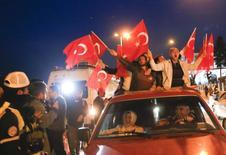 مؤيدو الرئيس التركي رجب طيب إردوغان يلوحون بأعلام بلدهم في اسطنبول يوم الاحد. تصوير: مراد سيزار - رويترز.