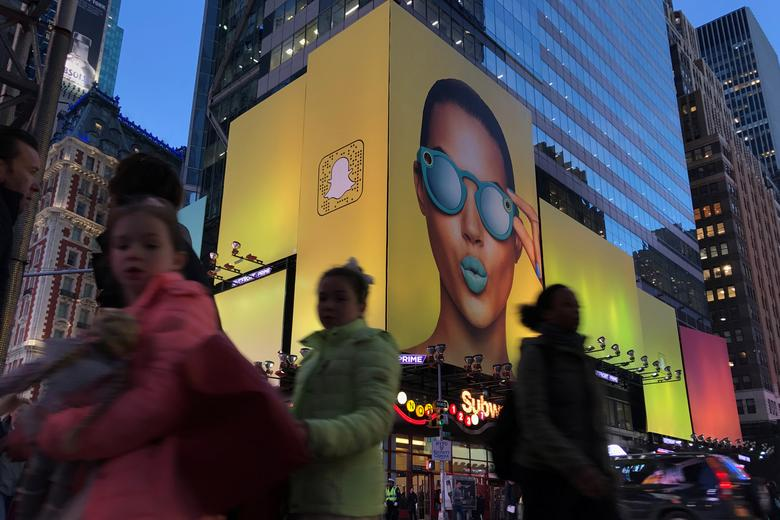 FILE PHOTO - People walk past a Snap Inc. billboard with a logo in Times Square in the Manhattan borough of New York, New York, U.S. March 21, 2017.   REUTERS/Carlo Allegri/File Photo