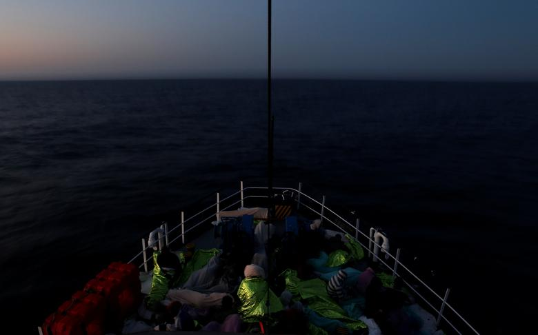 FILE PHOTO: Migrants rest on the Malta-based NGO Migrant Offshore Aid Station (MOAS) ship Phoenix after being rescued in the central Mediterranean off the Libyan coast, as the ship makes its way towards Italy at dusk, April 17, 2017.    REUTERS/Darrin Zammit Lupi