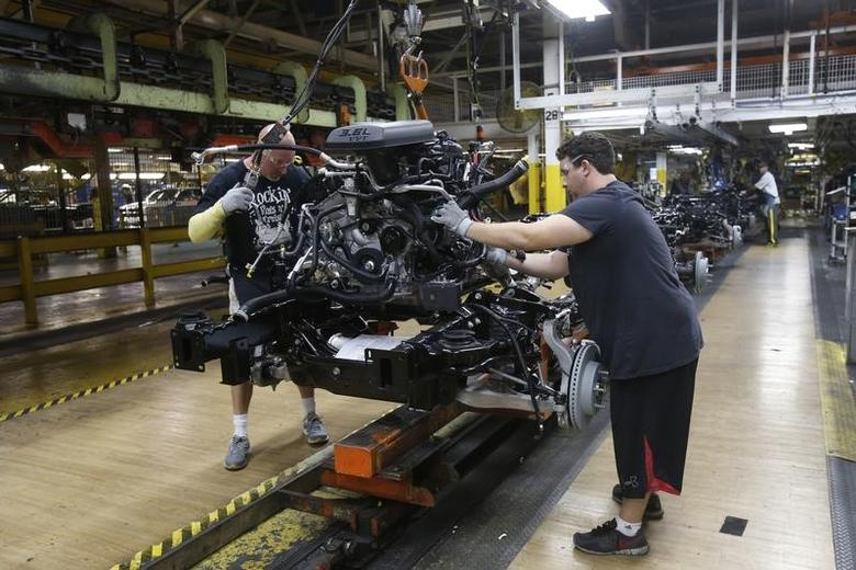 Chrysler Group assembly workers lower an engine onto the frame of a 2014 Ram 1500 pickup truck on the assembly line at the Warren Truck Plant during a tour of the plants redesigned work stations in Warren, Michigan, September 25, 2014.   REUTERS/Rebecca Cook