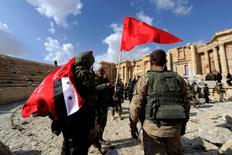 Syrian army soldiers carry flags in the amphitheater of the historic city of Palmyra, Syria March 4, 2017. REUTERS/Omar Sanadiki - RTS11FF9