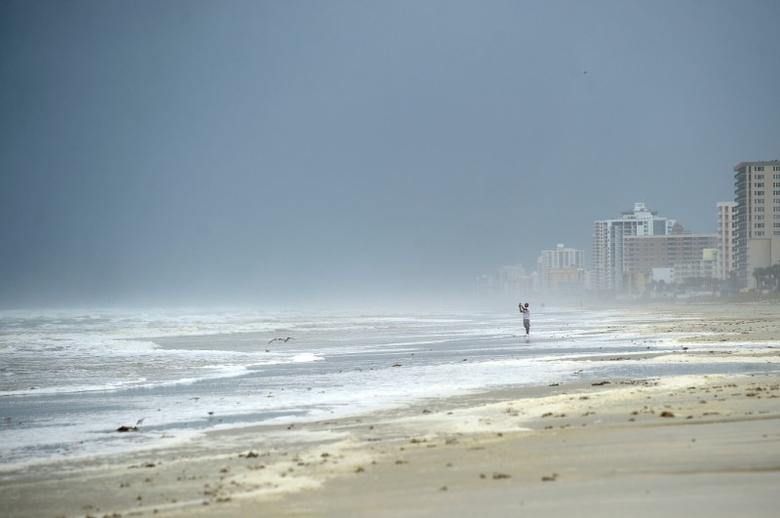 A beachgoer photographs the waves as a band of Hurricane Matthew arrives in Daytona Beach, Florida, U.S. October 6, 2016.  REUTERS/Phelan Ebenhack