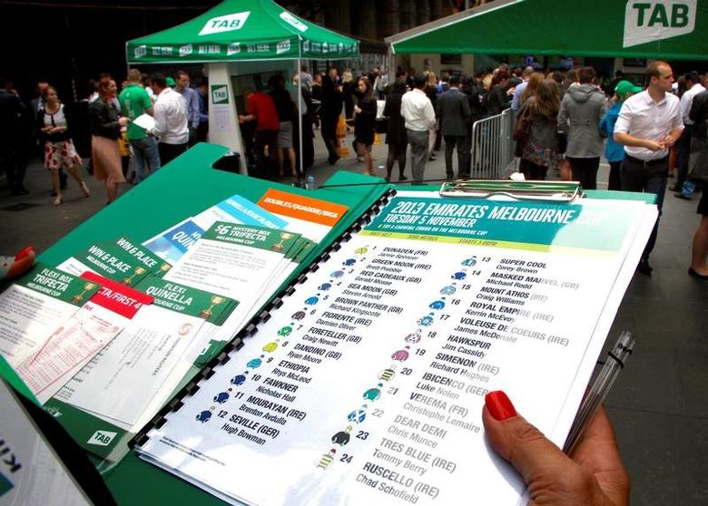 FILE PHOTO: An official holds a list of the Melbourne Cup horses and jockeys as people place bets at an outdoor betting tent organised by Australian gambling company Tabcorp Holdings Ltd (TAB) in central Sydney, Australia, November 5, 2013.  REUTERS/David Gray