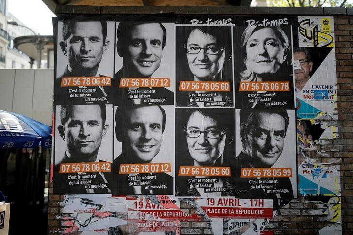 A poster campaign with factice portable cellphone numbers for French presidential candidates, Top row from L, Benoit Hamon, Socialist Party candidate, Emmanuel Macron, candidate for ''En Marche !'' or (Onwards !),  Nathalie Arthaud, candidate for France's extreme-left Lutte Ouvriere, and Marine Le Pen, the National Front (FN) leader and candidate; Bottom row R, Francois Fillon, the Republicans centre-right candidate, are seen on a wall in Paris, France, April 19, 2017.   REUTERS/Benoit Tessier
