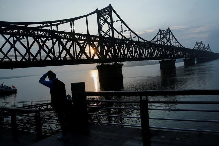 资料图片:2016年9月,一名男子在丹东鸭绿江大桥旁看日出。REUTERS/Thomas Peter