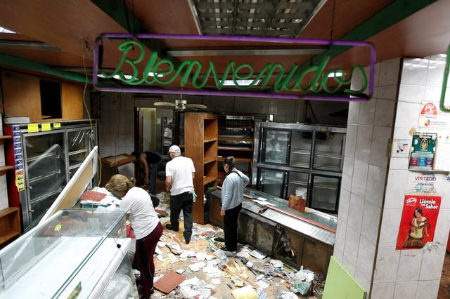 Workers look for valuables among the damaged goods in a bakery after it was looted in Caracas, Venezuela April 20, 2017. REUTERS/Christian Veron