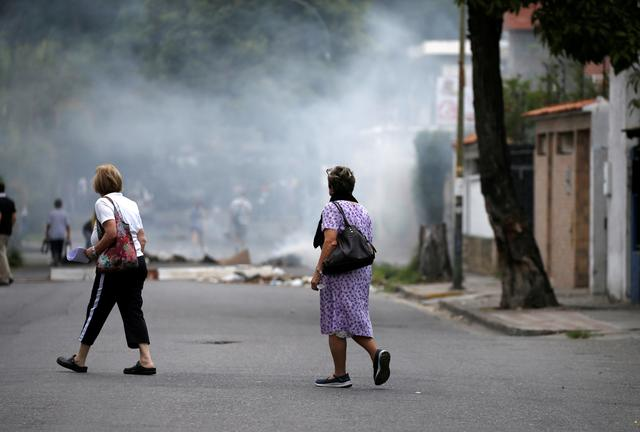 Women walk past a barricade set up by opposition supporters during a rally against Venezuela's President Nicolas Maduro in Caracas, Venezuela, April 20, 2017. REUTERS/Carlos Garcia Rawlins
