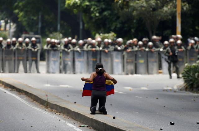 A demonstrator knees in front of riot police during a rally against Venezuela's President Nicolas Maduro in Caracas, Venezuela April 20, 2017. REUTERS/Carlos Garcia Rawlins