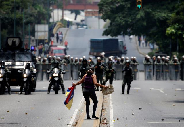 A demonstrator gestures while facing riot police during a rally against Venezuela's President Nicolas Maduro in Caracas, Venezuela, April 20, 2017. REUTERS/Carlos Garcia Rawlins