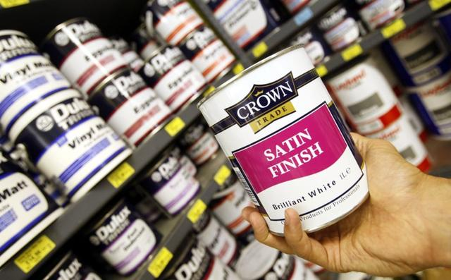 A can of Crown paint, produced by Akzo Nobel, is held up for the camera beside Dulux paint tins, produced by ICI,  at a decorators trade store in London, August 13, 2007. REUTERS/Toby Melville
