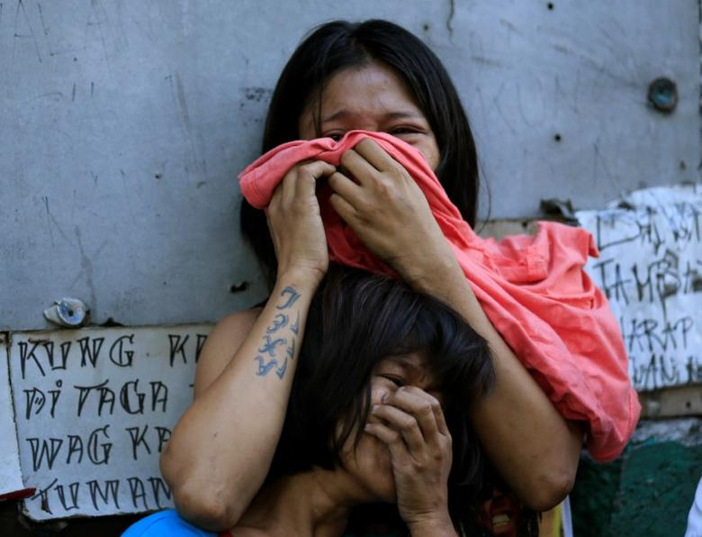Relatives of a suspected drug pusher, who was shot and killed by unidentified men, react upon learning that their kin was killed in Quezon city, metro Manila, Philippines March 7, 2017. REUTERS/Romeo Ranoco