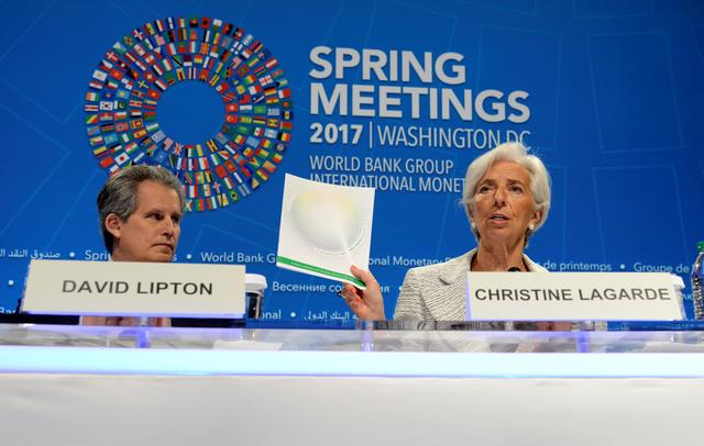 IMF Managing Director Christine Lagarde (R) holds up agenda papers as she attends a press briefing to open the IMF and World Bank's 2017 Annual Spring Meetings, with First Deputy David Lipton, in Washington, U.S., April 20, 2017.   REUTERS/Mike Theiler