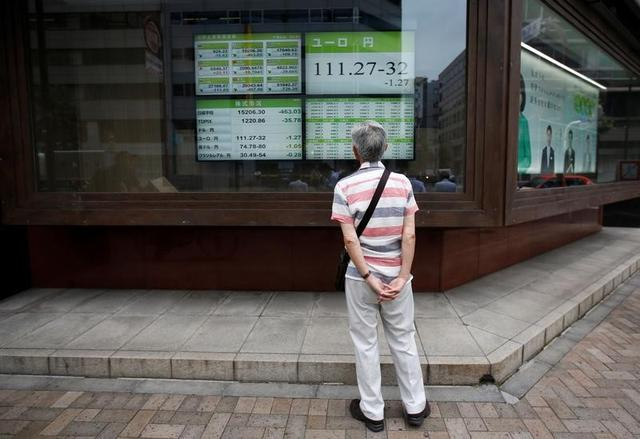A man looks at an electronic board outside a brokerage in Tokyo, Japan, July 6, 2016. REUTERS/Issei Kato