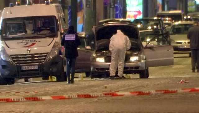 REFILE - CORRECTING CASUALTY NUMBER  A still image from video footage shows Police investigators inspect the car used by the attacker on the Champs Elysees Avenue after a policeman was killed and two others were wounded in a shooting incident in Paris, France, April 20, 2017.    REUTERS/Reuters Tv