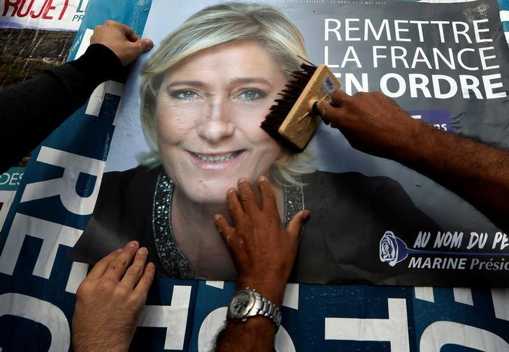 Members of the French National Front (FN) political party paste a poster on a free billboard for French National Front (FN) political party leader Marine Le Pen as part of the 2017 French presidential election campaign in Antibes, France, April 14, 2017.   REUTERS/Eric Gaillard