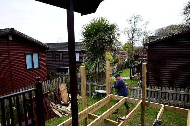 A worker extends a decking to a mobile home at The Thatchers Holiday Village in Modbury, Devon, Britain April 12, 2017. REUTERS/Dylan Martinez