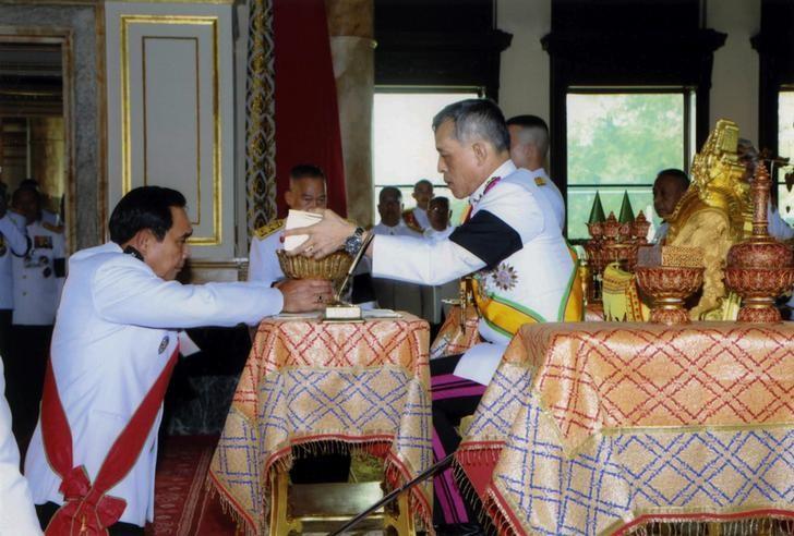 Thailand's King Maha Vajiralongkorn Bodindradebayavarangkun (R) returns the constitution after signing it to Thailand's Prime Minister Prayut Chan-o-cha at Ananta Samakhom Throne Hall in Bangkok, Thailand April 6, 2017. Thailand Royal Household Bureau/Handout via REUTERS/Files