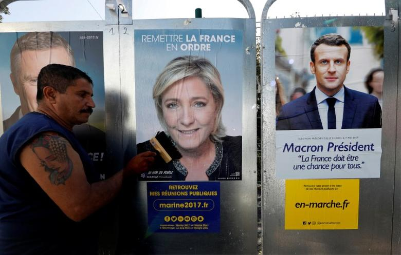 Sauveur, a member of the French National Front (FN) political party pastes a poster on an official billboard for French National Front (FN) political party leader Marine Le Pen next to the poster of  Emmanuel Macron (R), head of the political movement En Marche! (Onwards!), as part of the 2017 French presidential election campaign in Antibes, France, April 14, 2017.  REUTERS/Eric Gaillard/Files